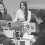Four graduate students work at a table together on big data projects
