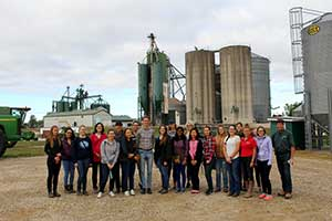 Students stand in front of a seed mill