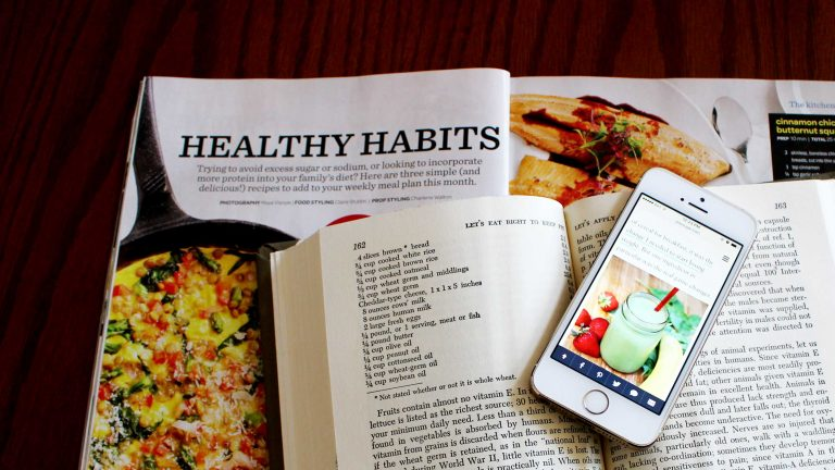 A phone sits on a cookbook and magazine about food