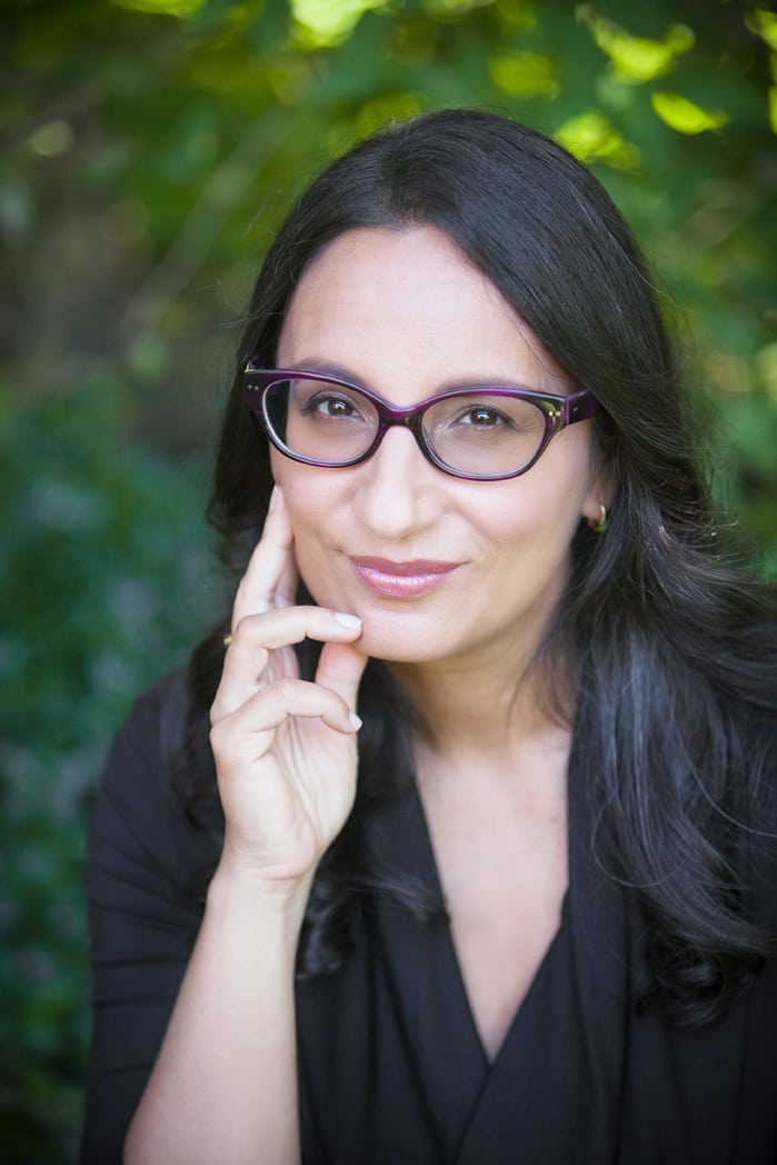 Image of Prof. Madhur Anand wearing a black top and with a hand resting on her face