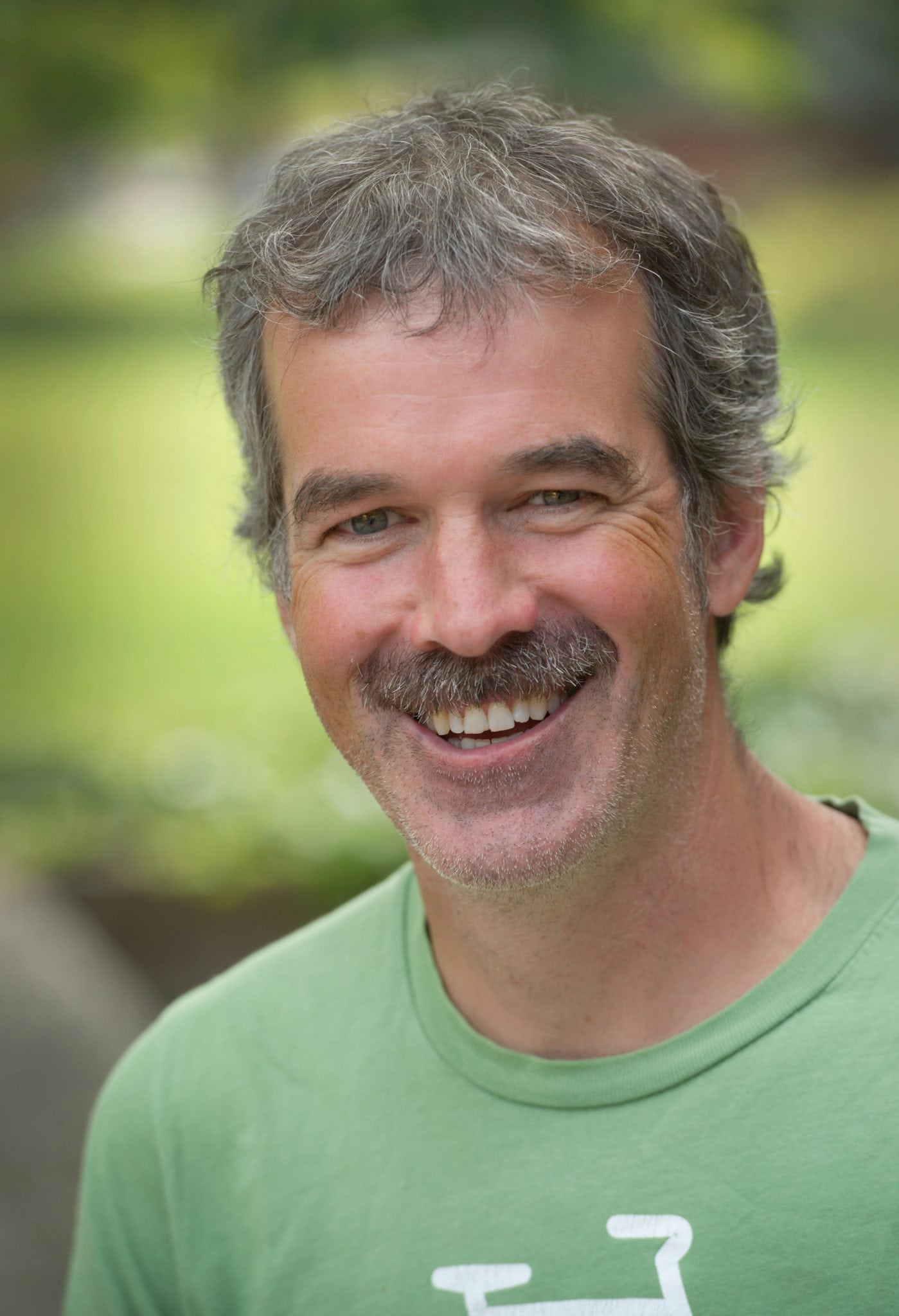 Photo of Prof. John Cant smiling in a green t-shirt