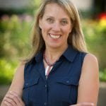 Photo of Prof. Kari Dunfield smiling with arms crossed and wearing a navy shirt