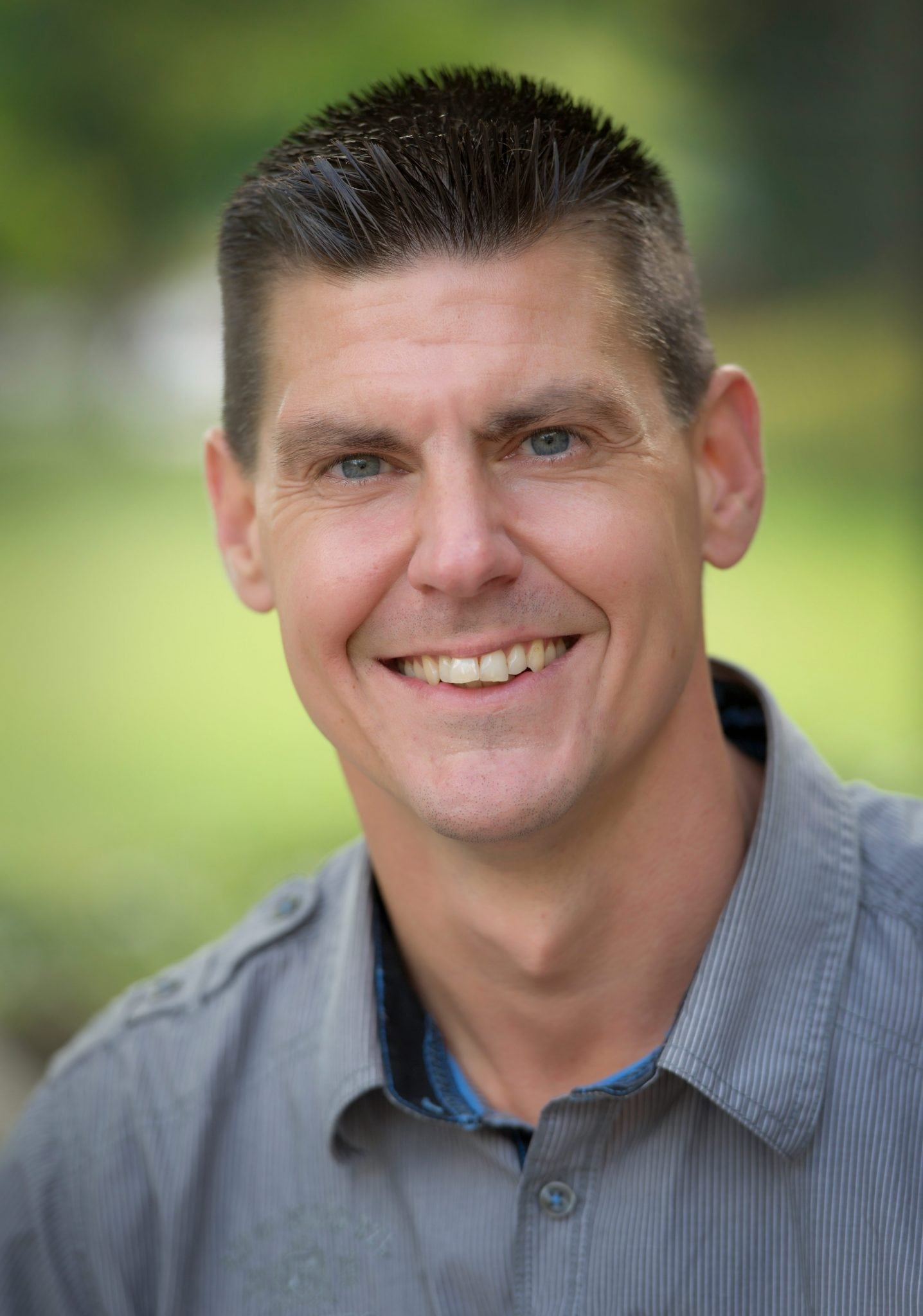 Photo of Prof. Trevor DeVries smiling and wearing a blue collared shirt