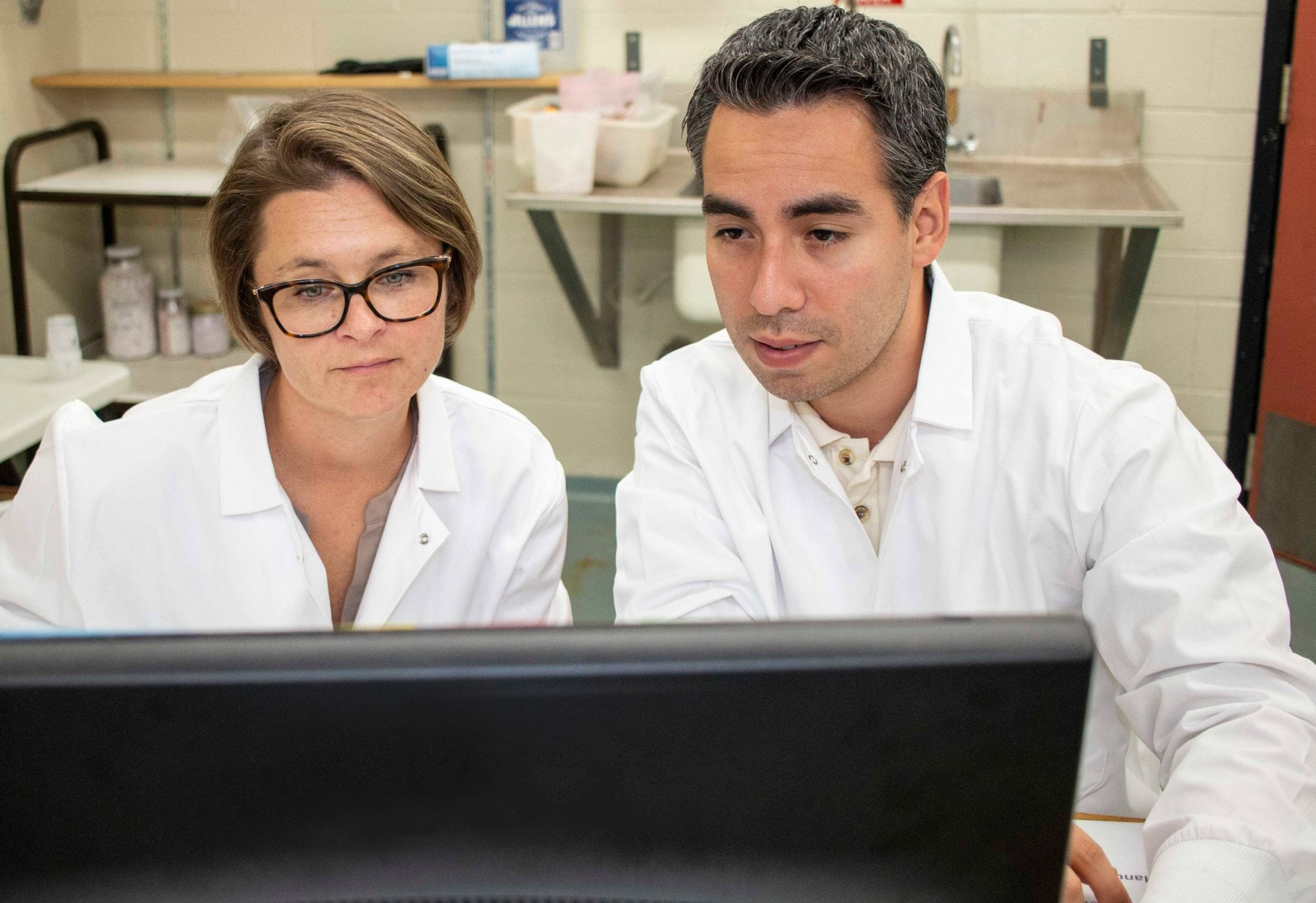 Food from Thought principal investigator Kate Shoveller and postdoc Wilfredo Mansillo sitting behind a computer in a lab.