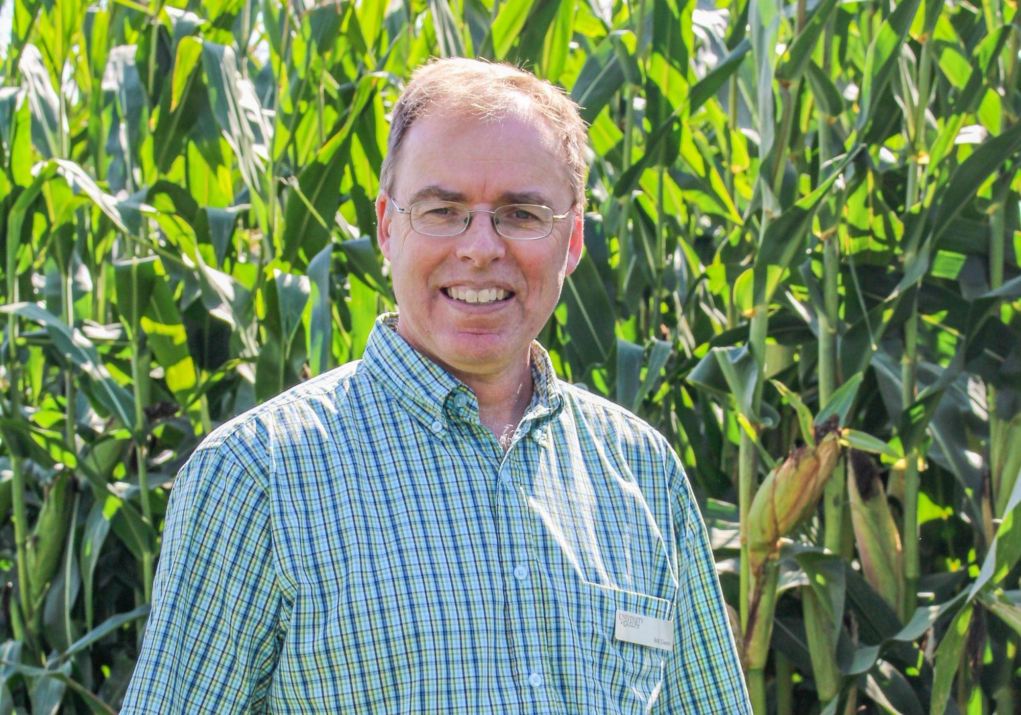 Prof. Bill deen standing in front of corn