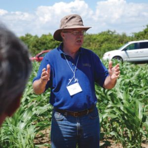 Prof. Clarence Swanton speaking in front of crops
