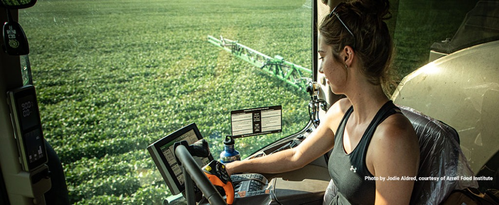 Image of woman in tractor looking at field and data